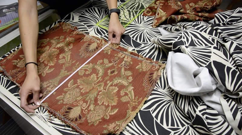 Serena Appiah of Thrift Diving measures fabric for the reupholstered bench